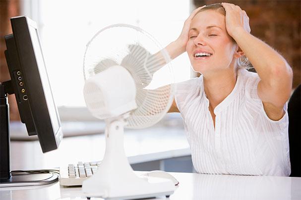 Термальная вода освежает - девушка в офисе под вентилятором